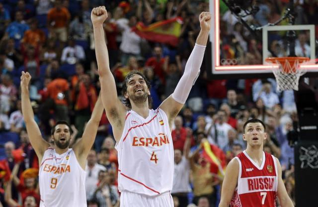 FILE - Spain's Pau Gasol (4) and teammate Felipe Reyes (9) celebrate their win over Russia in a semifinal men's basketball game at the 2012 Summer Olympics in London, in this Friday, Aug. 10, 2012, file photo. Russia's Vitaliy Fridzon is at right. Pau Gasol announced his retirement from basketball on Tuesday, Oct. 5, 2021, ending a career that lasted more than two decades and earned him two NBA titles and a world championship gold with Spain's national team. (AP Photo/Eric Gay, File)