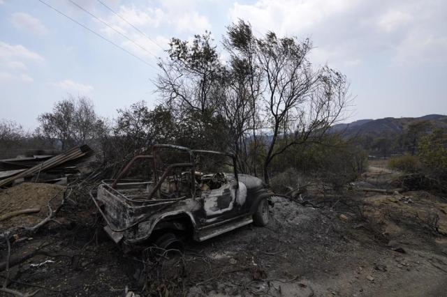 """A burned car is seen on Troodos mountain, in Ora village, southwestern Cyprus, Sunday, July 4, 2021. Cyprus search crews discovered the bodies of four people outside a fire-swept mountain village on Sunday in what a government minister called the """"most destructive"""" blaze in the east Mediterranean island nation's history. (AP Photo/Petros Karadjias)"""
