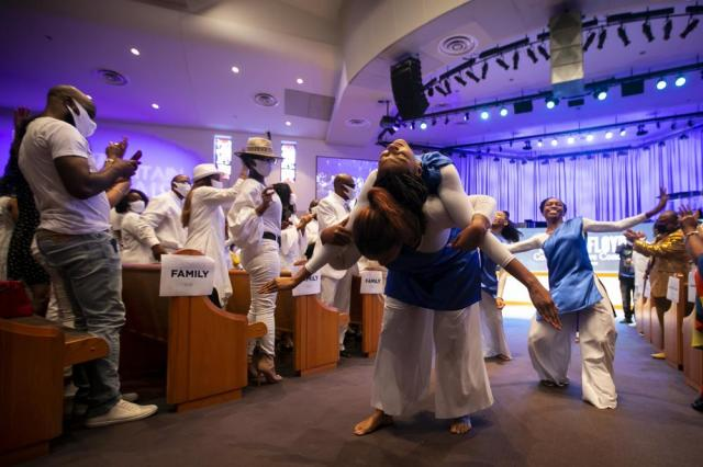 Members of The Fountain of Praise C.R.O.S.S. Praise Dance team perform in the aisle during a commemorative concert hosted by the George Floyd Foundation at The Fountain of Praise church on Sunday, May 30, 2021, in Houston. Musicians, elected officials and community members joined the family of George Floyd to reflect on his life and the year of fighting for social justice since his murder. (Annie Mulligan/Houston Chronicle via AP)