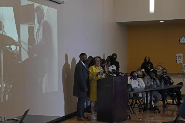 """Marcia Carter-Patterson, second from left, the mother of Manuel """"Manny"""" Ellis, stands with family members as she speaks Thursday, May 27, 2021, at a news conference in Tacoma, Wash., south of Seattle. Ellis, who is shown in the photo playing drums in church, died on March 3, 2020 after he was restrained by police officers. Earlier in the day Thursday, Washington state attorney general filed criminal charges against three police officers in the death of Ellis. (AP Photo/Ted S. Warren)"""