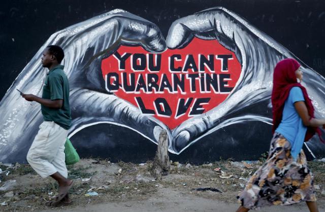 Pedestrians walk past a coronavirus information mural on a street in Mombasa, Kenya Monday, Sept. 27, 2021. (AP Photo/Brian Inganga)