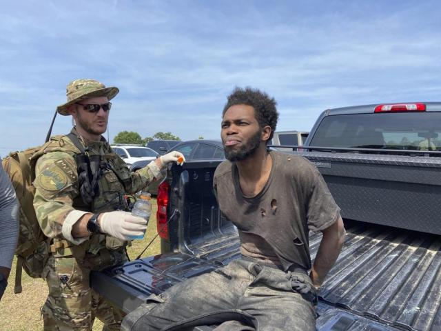 In this photo provided by the Chester County Sheriff's Office, Tyler Terry is offered water during his arrest in South Carolina on Monday, May 24, 2021. A weeklong manhunt for Terry, a suspect wanted in the killings of four people, ended without another shot fired as hundreds of officers surrounded him, authorities said. (Chester County Sheriff's Office via AP)