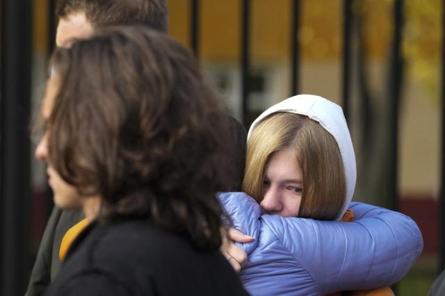 Students react standing outside the Perm State University in Perm, about 1,100 kilometers (700 miles) east of Moscow, Russia, Tuesday, Sept. 21, 2021. A student opened fire at the university, leaving a number of people dead and injured, before being shot in a crossfire with police and detained. Beyond saying that he was a student, authorities offered no further information on his identity or a possible motive. (AP Photo/Dmitri Lovetsky)