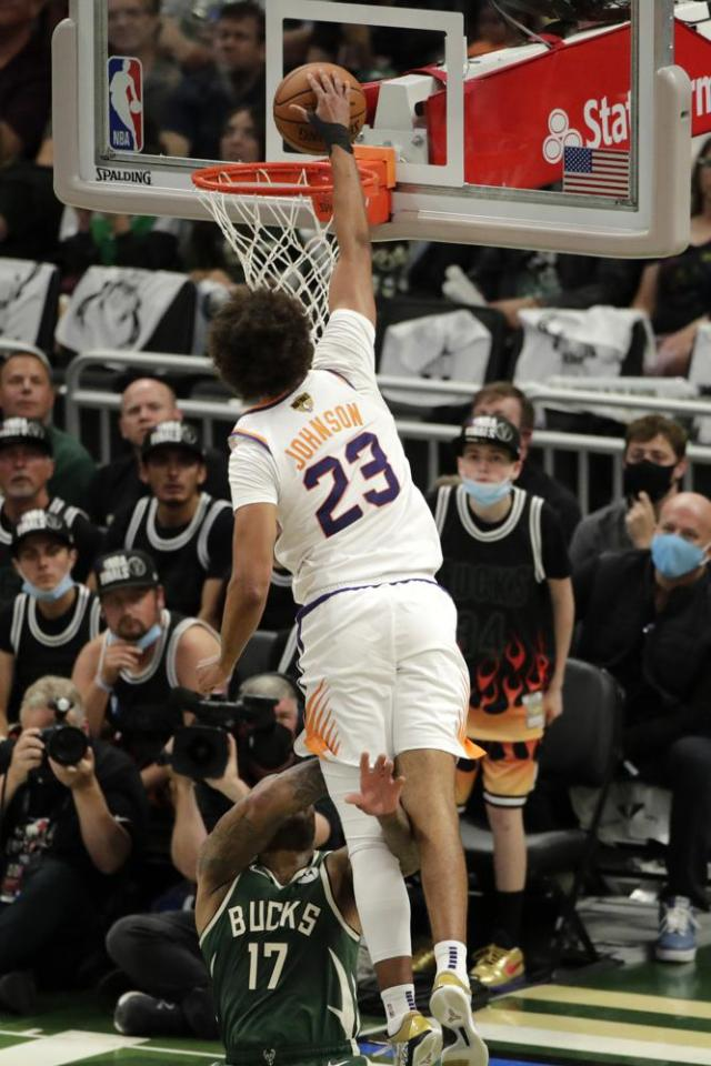 Phoenix Suns' Cameron Johnson (23) dunks as he's fouled by Milwaukee Bucks' P.J. Tucker (17) during the second half of Game 3 of basketball's NBA Finals, Sunday, July 11, 2021, in Milwaukee. (AP Photo/Aaron Gash)