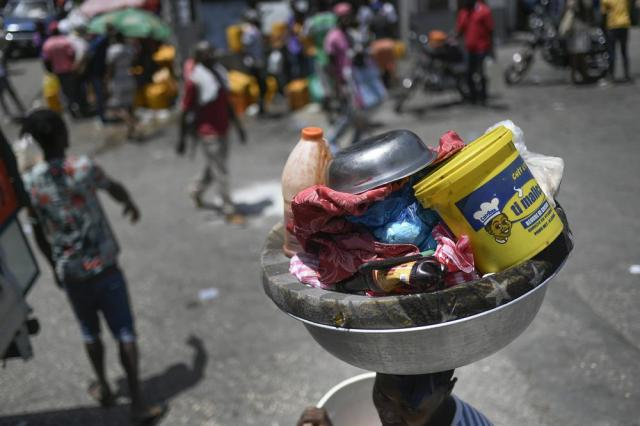 A woman carries a basin with her belongings at the Petion-Ville market in Port-au-Prince, Haiti, Sunday, July 11, 2021, four days after the assassination of Haitian President Jovenel Moise. (AP Photo/Matias Delacroix)
