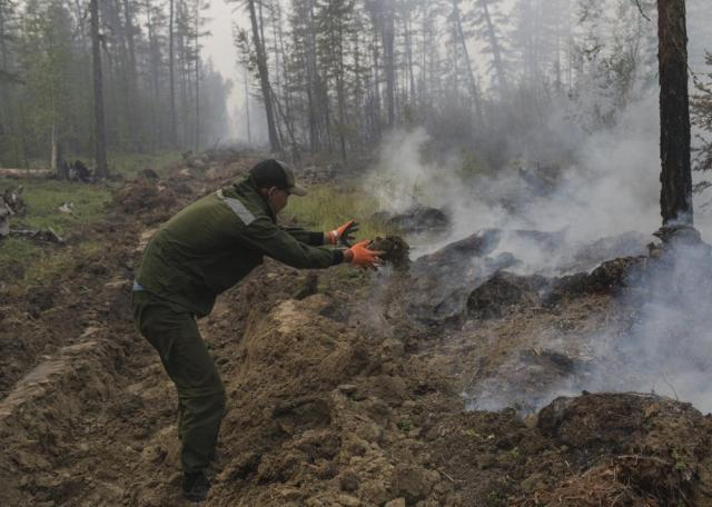 A volunteer helps dig a firebreak to stop a forest fire outside Magaras village 87 km. (61 miles) west of Yakustk, the capital of the republic of Sakha also known as Yakutia, Russia Far East, Sunday, July 18, 2021. Russia has been plagued by widespread forest fires, blamed on unusually high temperatures and the neglect of fire safety rules, with the Sakha-Yakutia region in northeastern Siberia being the worst affected. (AP Photo/Alexey Vasilyev)