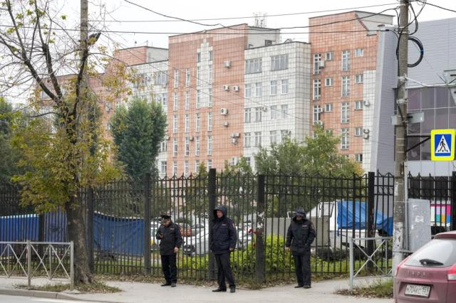 Police officers stand guard in front of the fence and the building where the gunman opened fire at the Perm State University in Perm, about 1,100 kilometers (700 miles) east of Moscow, Russia, Tuesday, Sept. 21, 2021. A student opened fire at the university, leaving a number of people dead and injured, before being shot in a crossfire with police and detained. Beyond saying that he was a student, authorities offered no further information on his identity or a possible motive. (AP Photo/Dmitri Lovetsky)