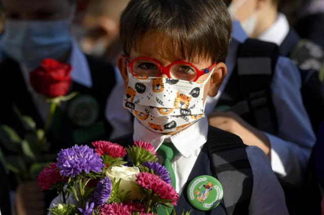 A boy wearing a face mask holds flowers during festivities marking the beginning of the school year at a school in Bucharest, Romania, Monday, Sept. 13, 2021. Children returned to classrooms in Romania, a country with one of the lowest COVID-19 vaccination rates in the European Union, as the daily infection numbers continue to rise. (AP Photo/Andreea Alexandru)