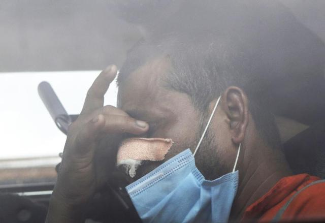 A man rescued by the Indian navy from a barge that sank in the Arabian sea and brought by Indian naval ship INS Kochi reacts as he sits inside a vehicle in Mumbai, India, Wednesday, May 19, 2021. The barge carrying personnel deployed for offshore drilling sank off Mumbai as a deadly cyclone blew ashore this week. (AP Photo/Rajanish Kakade)