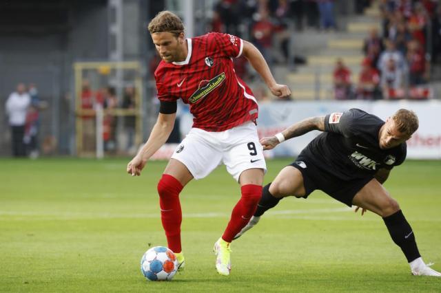 Freiburg's Lucas Hoeler, left, and Augsburg's Niklas Dorsch vie for the ball during their Bundesliga soccer match in Freiburg, Germany, Sunday, Sept. 26, 2021. (Philipp von Ditfurth/dpa via AP)