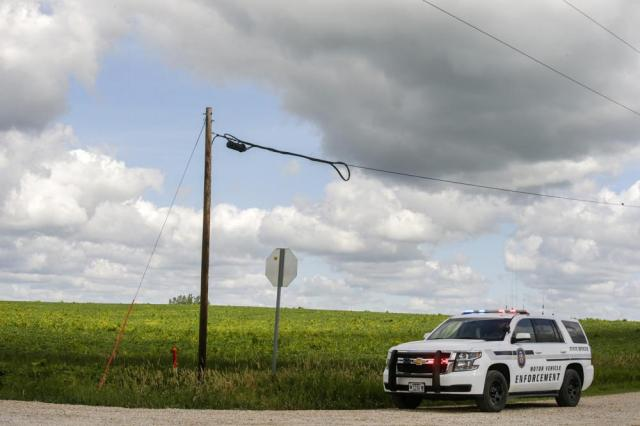 An officer with Iowa Motor Vehicle Enforcement parks at the intersection of Linn Delaware Rd. And 140th Avenue in Coggon, Iowa, on Monday, June 21, 2021. A Chicago man who allegedly shot and wounded a sheriff's deputy at an Iowa gas station and then evaded an extensive manhunt for hours has been arrested, a sheriff said Monday. (Jim Slosiarek/The Gazette via AP)