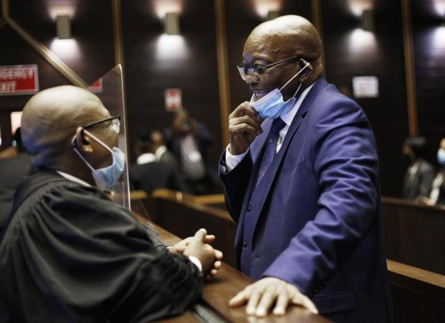 Former South African President Jacob Zuma, right, reacts,  in the High Court,  in Pietermaritburg, South Africa, Monday, May 17, 2021. Zuma and French arms company Thales face corruption, racketeering and money laundering charges linked to an arms deal. (Rogan Ward/Pool Photo via AP)