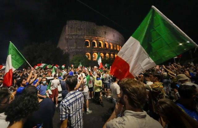 Italy's fans celebrate in front of the ancient Colosseum in Rome, Monday, July 12, 2021, after Italy beat England to win the Euro 2020 soccer championships in a final played at Wembley stadium in London. Italy beat England 3-2 in a penalty shoutout after a 1-1 draw. (AP Photo/Alessandra Tarantino)