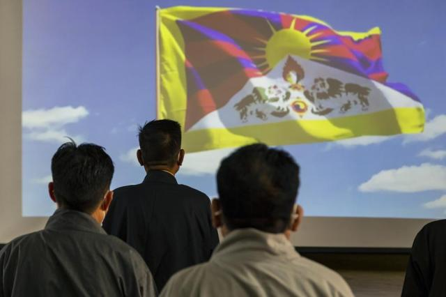 A video of the Tibetan flag is projected on a screen as the President of the Central Tibetan Administration Penpa Tsering, second left, stands up with other government officials for the Tibetan national anthem during a ceremony to mark the 86th birthday of their spiritual leader the Dalai Lama in Dharmsala, India, Tuesday, July 6, 2021.  (AP Photo/Ashwini Bhatia)