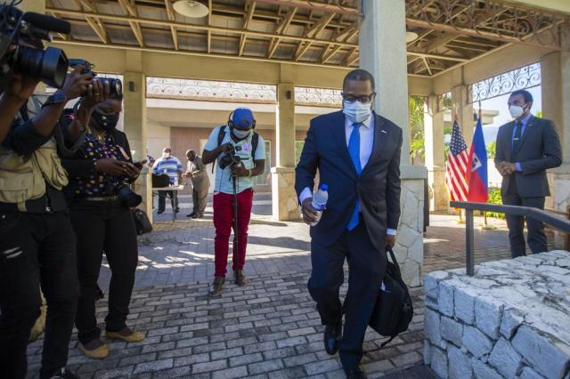 Assistant Secretary for Western Hemisphere Affairs Brian Nichols leaves at the end of a press conference at the U.S. Embassy, in Port-au-Prince, Haiti, Friday, Oct. 1, 2021. Nichols, who arrived in Haiti on Thursday, has meetings planned with Prime Minister Ariel Henry and Foreign Minister Claude Joseph to discuss future elections, migration, security and US support. (AP Photo/Joseph Odelyn)