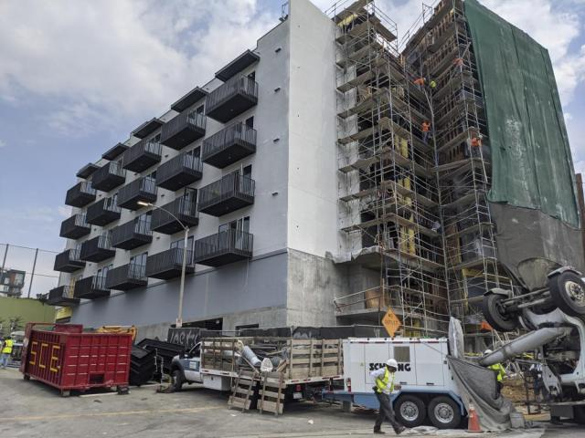 In this June 18, 2021, photo, construction workers finish the exterior of an apartment building downtown Los Angeles. California Gov. Gavin Newsom on Thursday, Sept. 16, 2021, approved two measures to slice through local zoning ordinances as the most populous state struggles with soaring home prices, an affordable housing shortage and stubborn homelessness. Newsom also signed a bill extending a 2019 law designed to make it easier to build more housing throughout the state. (AP Photo/Damian Dovarganes)