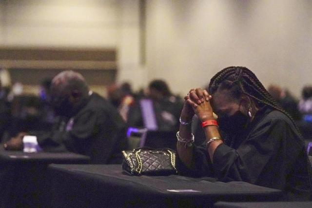Worshippers pray during the opening worship service at the African Methodist Episcopal Church conference Tuesday, July 6, 2021, in Orlando, Fla. (AP Photo/John Raoux)