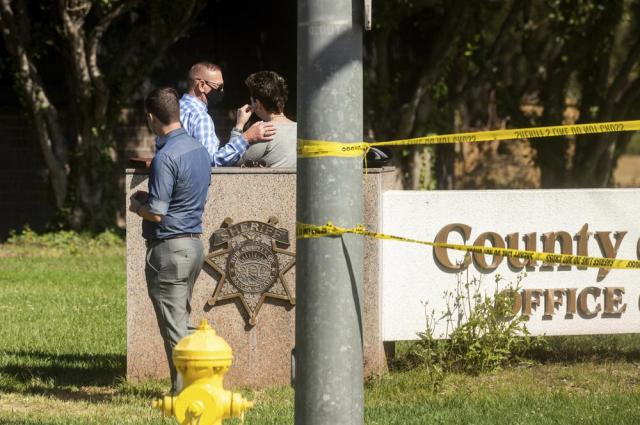 A man comforts a woman near the scene of a shooting at a Santa Clara Valley Transportation Authority (VTA) facility on Wednesday, May 26, 2021, in San Jose, Calif. Santa Clara County sheriff's spokesman said the railyard shooting left multiple people, including the shooter, dead. (AP Photo/Noah Berger)