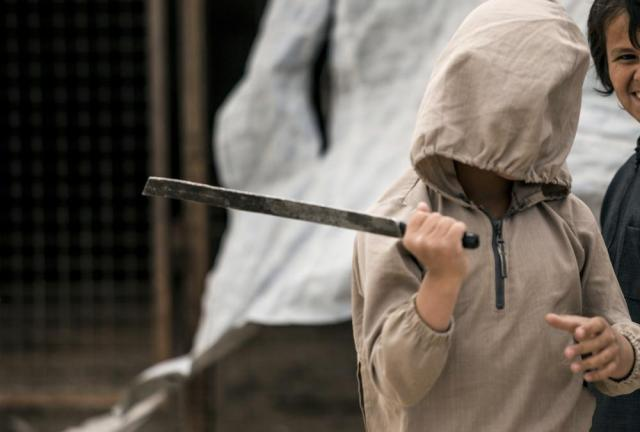A boy plays with a broken sword, at al-Hol camp, which houses families of members of the Islamic State group, in Hasakeh province, Syria, Saturday, May 1, 2021.   It has been more than two years that some 27,000 children have been left to languish in al-Hol camp, which houses families of IS members.   Most of them not yet teenagers, they are spending their childhood in a limbo of miserable conditions with no schools, no place to play or develop and seemingly no international interest in resolving their situation.   (AP Photo/Baderkhan Ahmad)