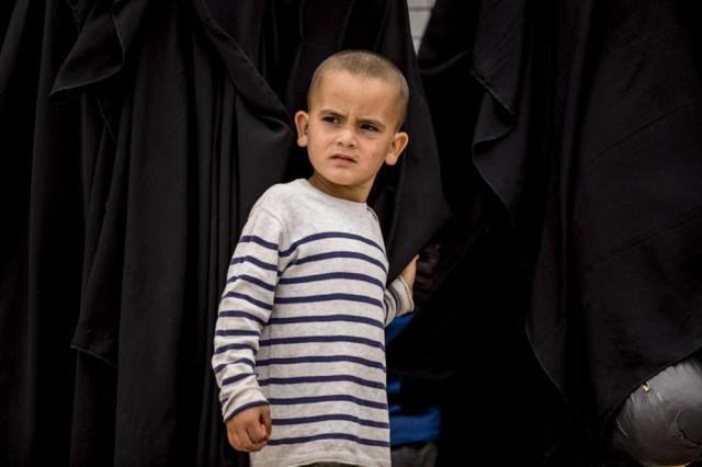 A boy stands next to his mother at al-Hol camp, which houses families of members of the Islamic State group, in Hasakeh province, Syria, Saturday, May 1, 2021. It has been more than two years that some 27,000 children have been left to languish in al-Hol camp. Most of them not yet teenagers, they are spending their childhood in a limbo of miserable conditions with no schools, no place to play or develop and seemingly no international interest in resolving their situation. (AP Photo/Baderkhan Ahmad)
