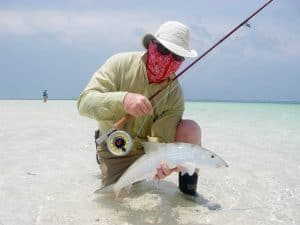 Fly fisher holding a catch in the flats. He is wearing a High Uv Buff® as face mask. The cooling effect makes the face mask comfortable. © Pat Ford http://www.patfordphotos.com/. Licenced by Original Buff S.A for the promotion of the High Uv Buff®