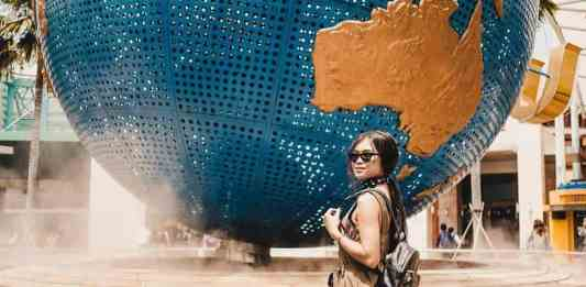 A girl posing in front of the USS Globe at the Universal Studios Singapore