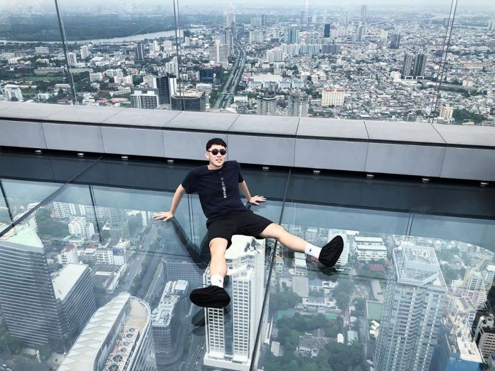A guy posing on the glass tray-paved Mahanakhon Skywalk