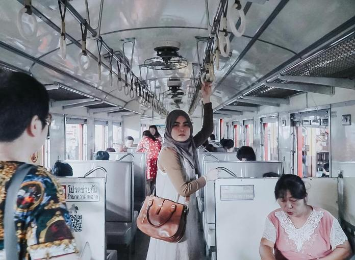 A girl traveling to Thailand and posing inside a train