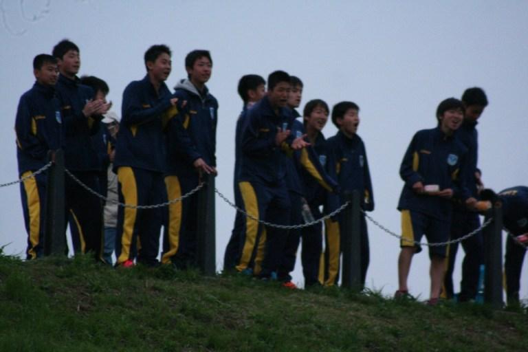 土手の上から声援を送る栃木SCの選手たち