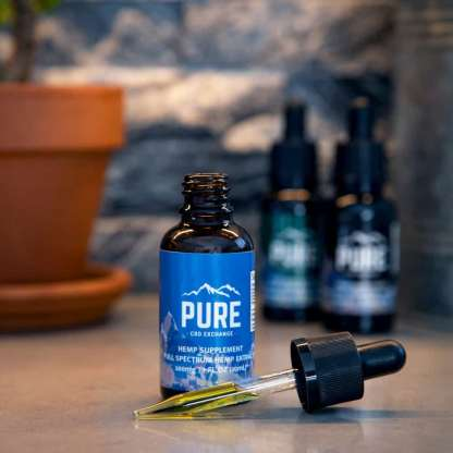 A Pure CBD Exchange Tincture sitting next to an eyedropper filled with tincture
