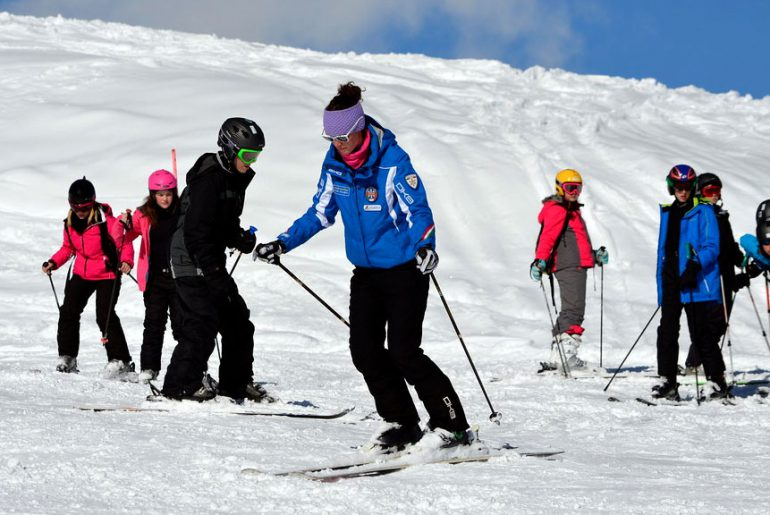 ski instructor in blue jacket leads kids group ski lesson