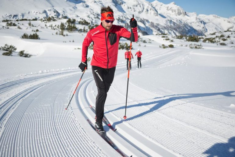 cross country skiers in red coming towards camera