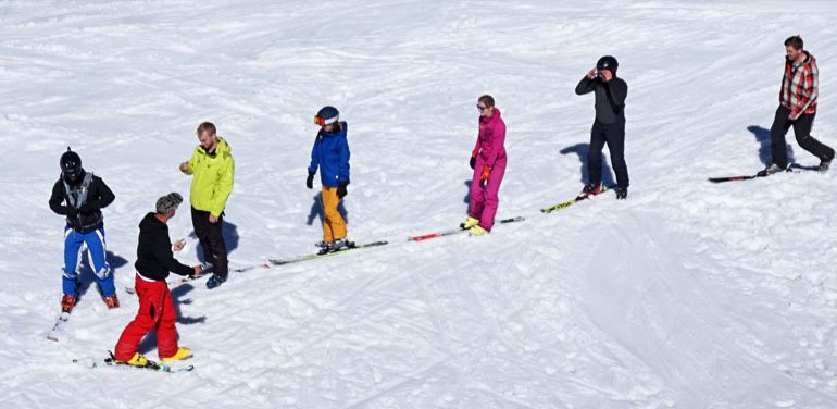 ski instructor teaches first timer adult skiers the one foot ski shuffle