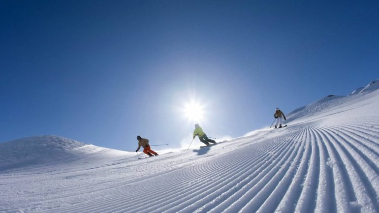 three skiers enjoy freshly groomed piste in the sun