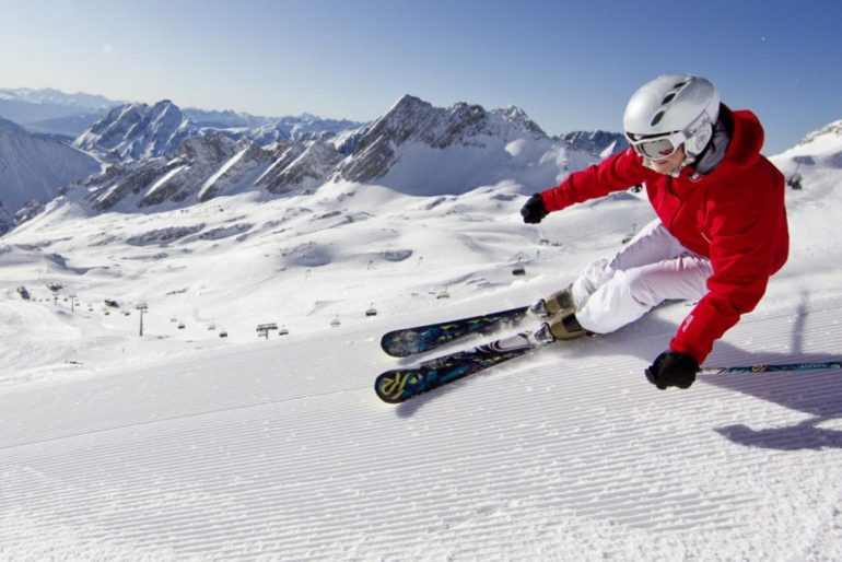 woman in red carving on skis