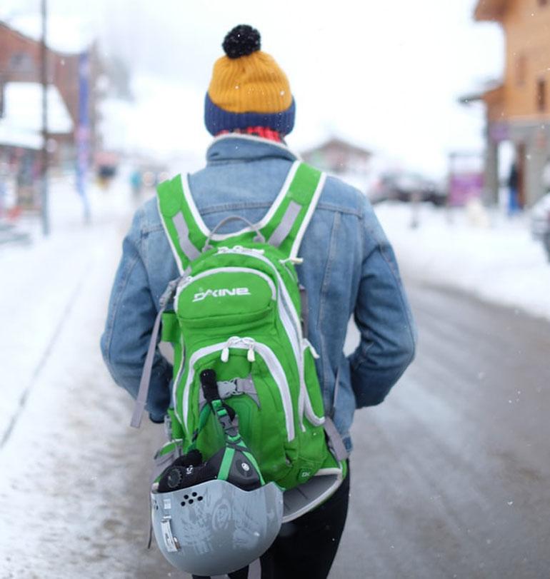 man in ski resort wearing ski backpack and ski helmet