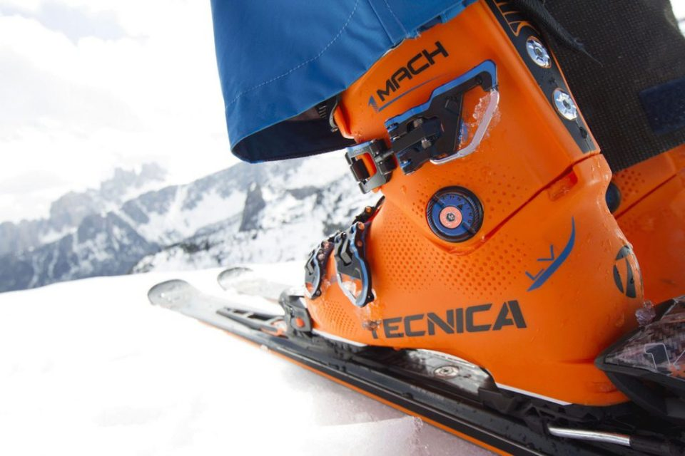 Orange ski boots clipping in to skis