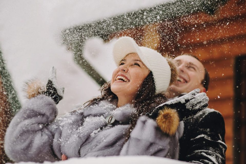 Stylish couple playing with snow in wooden cabin on background of winter snowy mountains