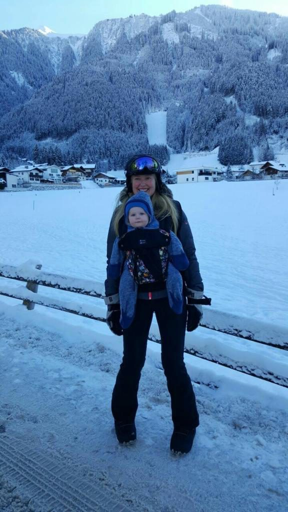 Woman with baby on chest in snowy mountain scenery