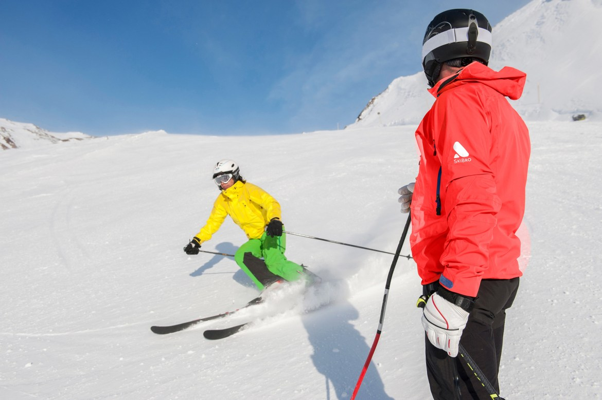 ski instructor in red jacket watches student carve on ski run
