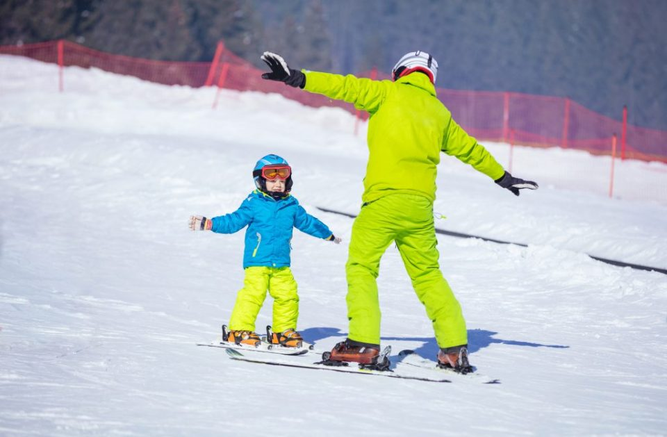 Lesson at skiing school: instructor teaching little skier how to make turns, young boy trying a snow plow turn on slope in children's area