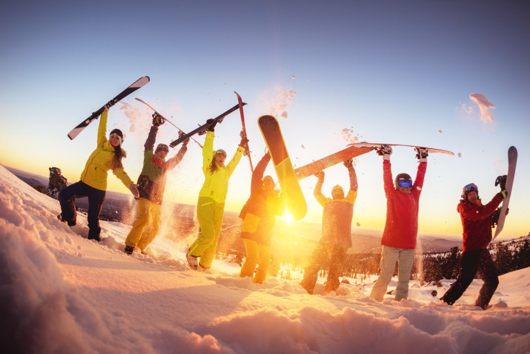 Group of happy friends skiers and snowboarders is having fun at ski resort against sunset