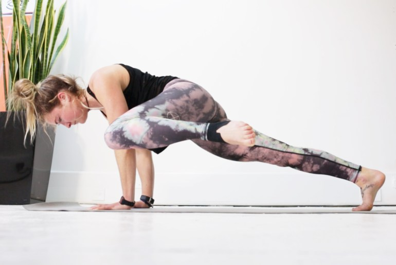 woman in gym leggings performs a leg raise exercise in her lounge room in preparation for a ski holiday