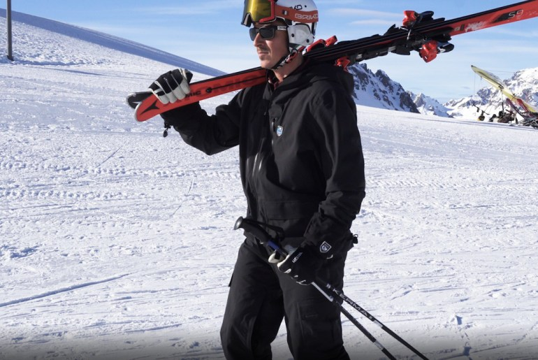 Ski instructor displays correct technique to carry skis