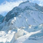 A view of three skiers admiring glaciers and seracs in Chamonix's Vallee Blanche