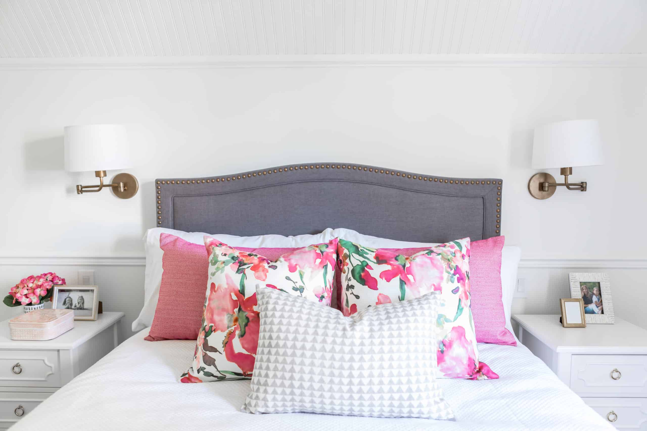 Colorful pillows on a white and purple bed