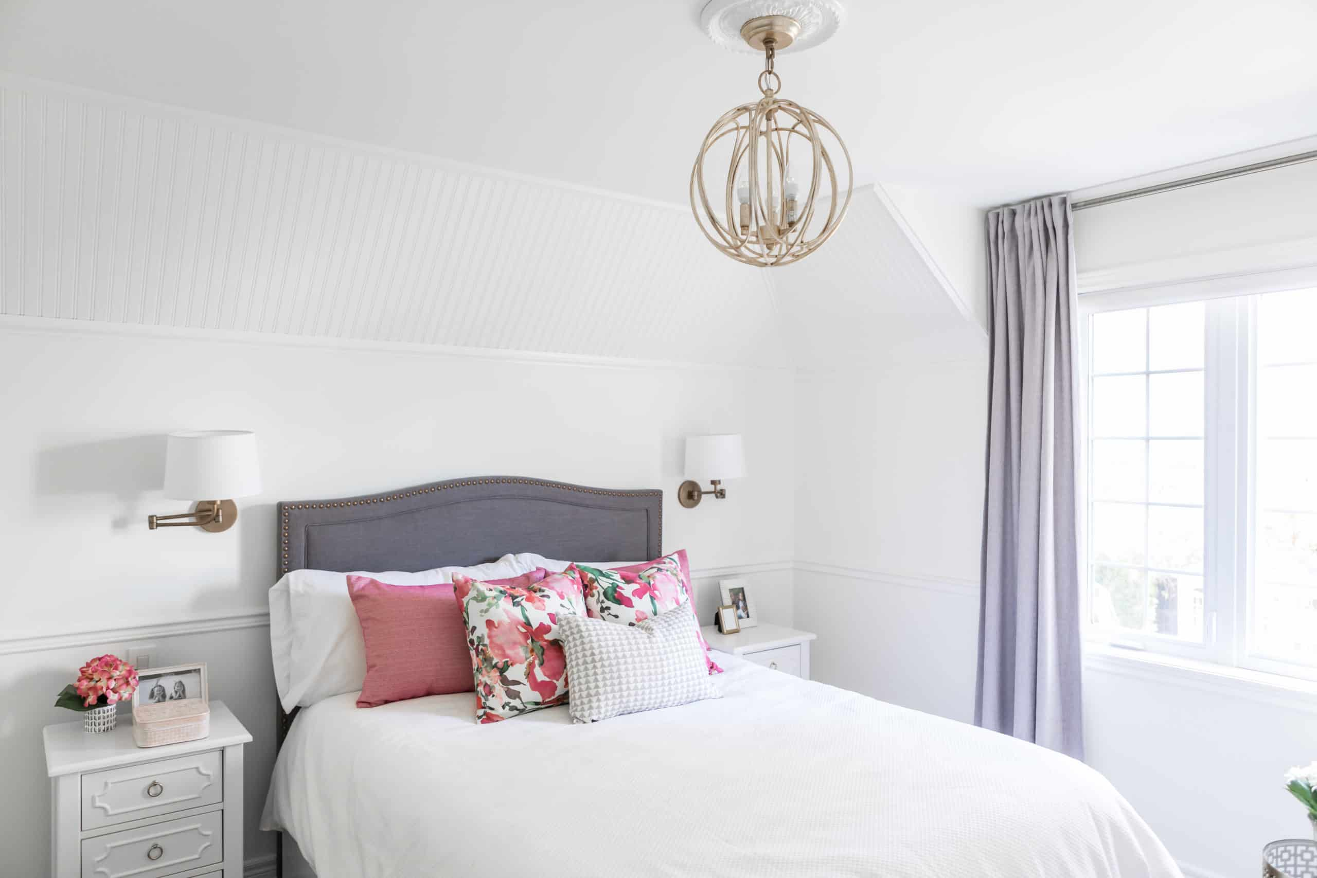 Spherical chandelier above a white and purple bed