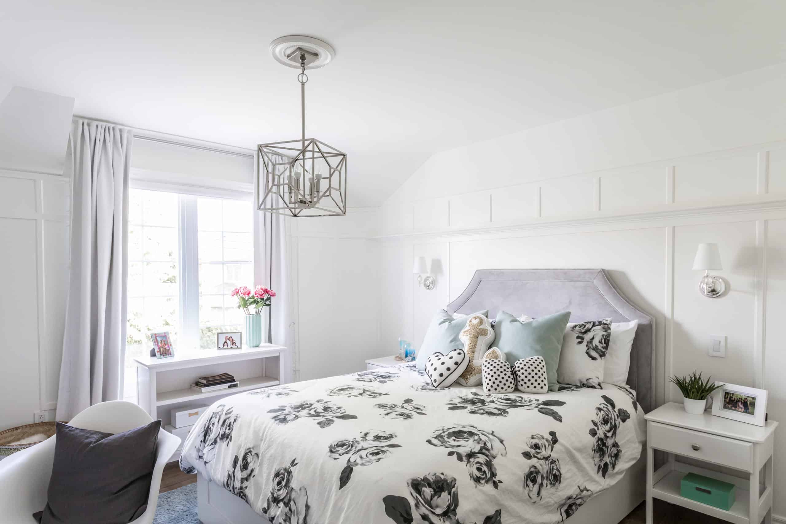 Cubic chandelier above a bed with a floral pattern on it