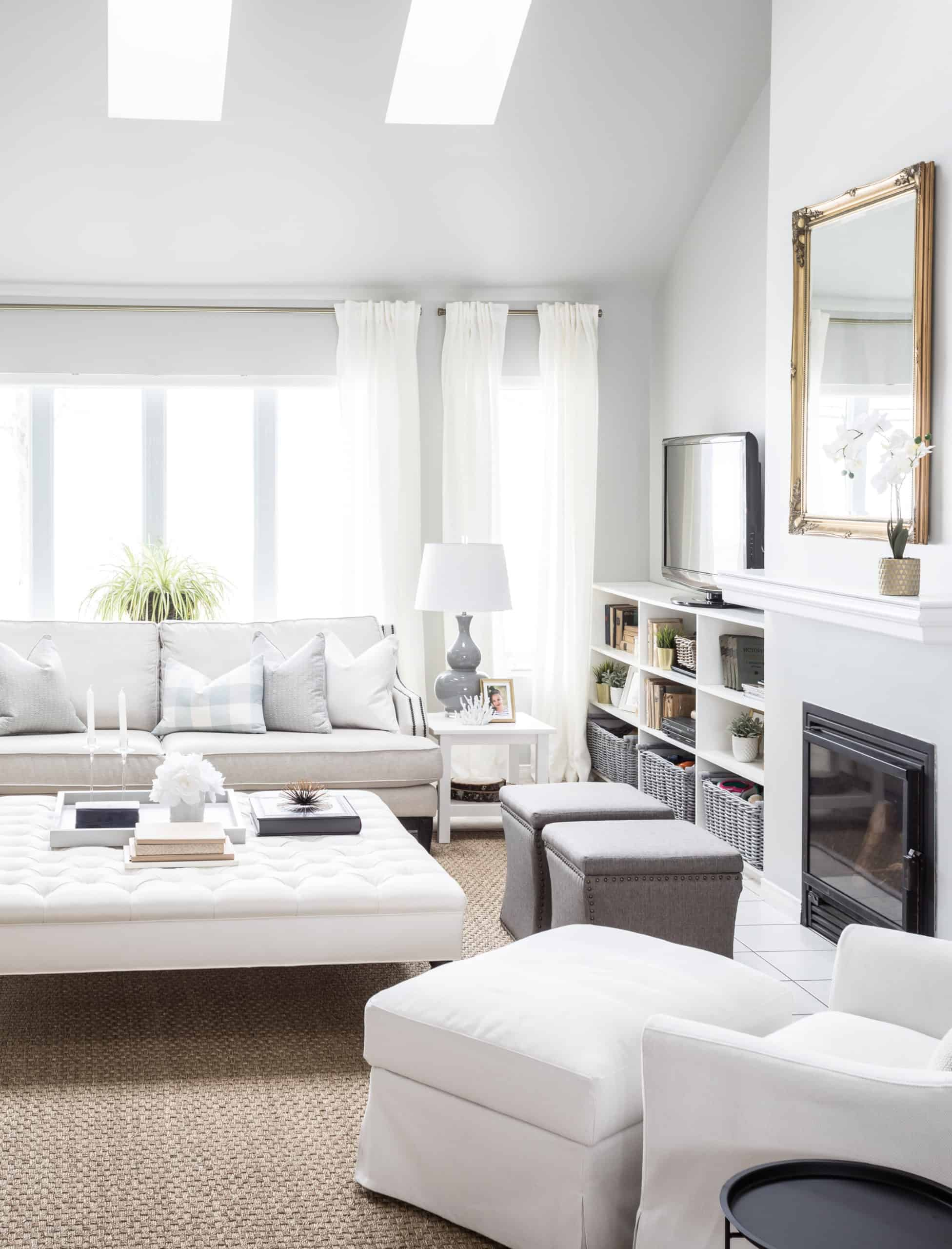 Large, modern living room with bright white furniture in it