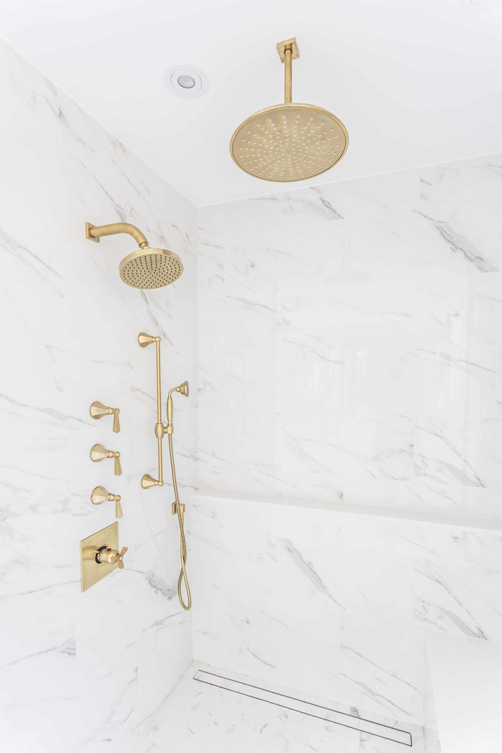 Golden faucet inside the shower covered in marble